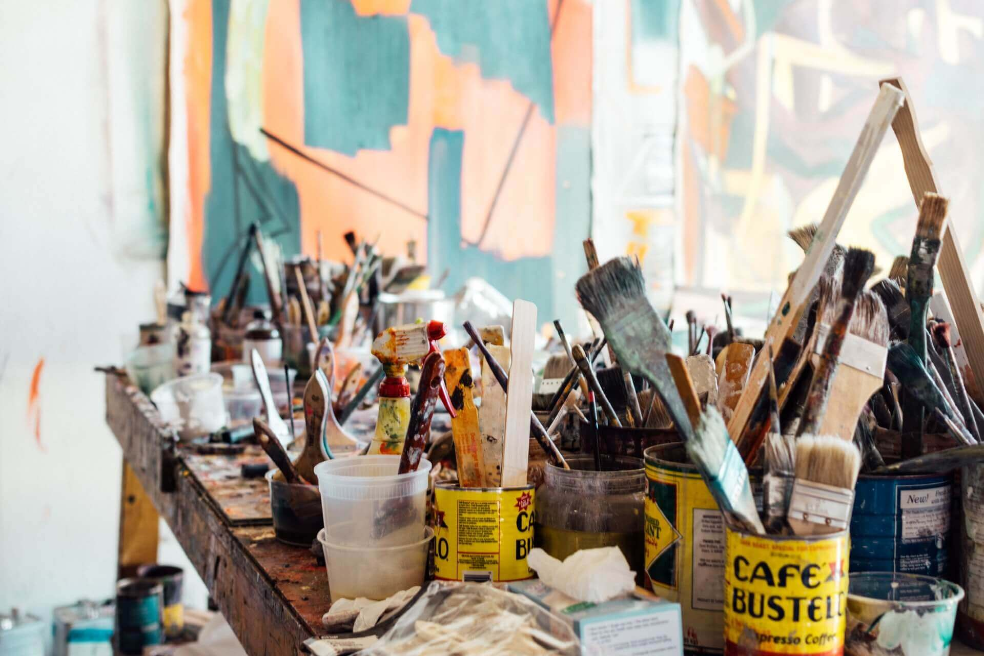 An image of assorted-colored paint brushes on brown wooden table top
