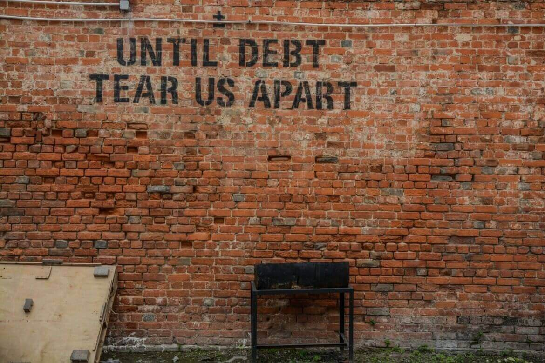 "A photo of a graffiti saying ""Until debt tear us apart"